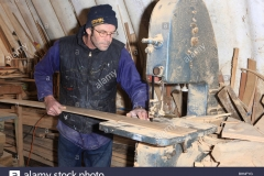 boat-builder-dave-currah-using-a-band-saw-in-his-workshop-at-looe-BHNFYG
